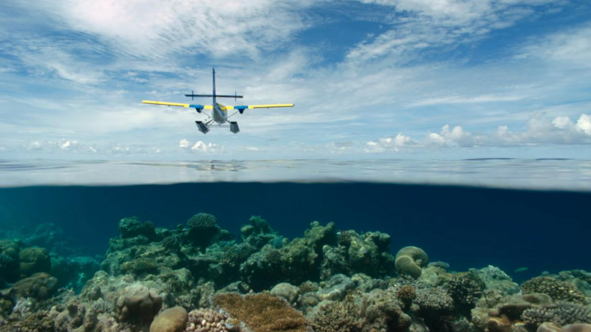 """Twin Otter seaplane flying over the shallow waters of the Maldives. Screenshot from the film """"Living in the Age of Airplanes,"""" to be released by National Geographic Studios on giant screens and digital cinemas worldwide April 10, 2015."""
